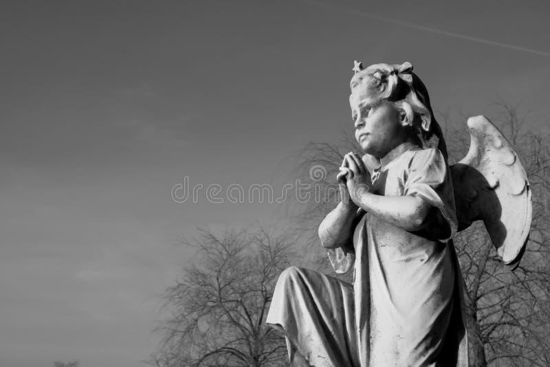 Engel die op één knie bidden stock fotografie