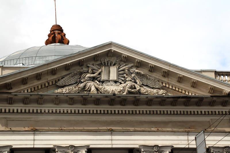 Engel halten heilige Schrift über der Fassade eines Altbaus mit Spalten stockfotografie