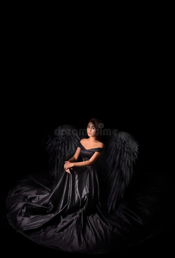 Engel-Teufelmodell im schwarzen langen Kleid mit den Flügeln, die im Studio sitzen Schwarzer Hintergrund, Innen stockfotos