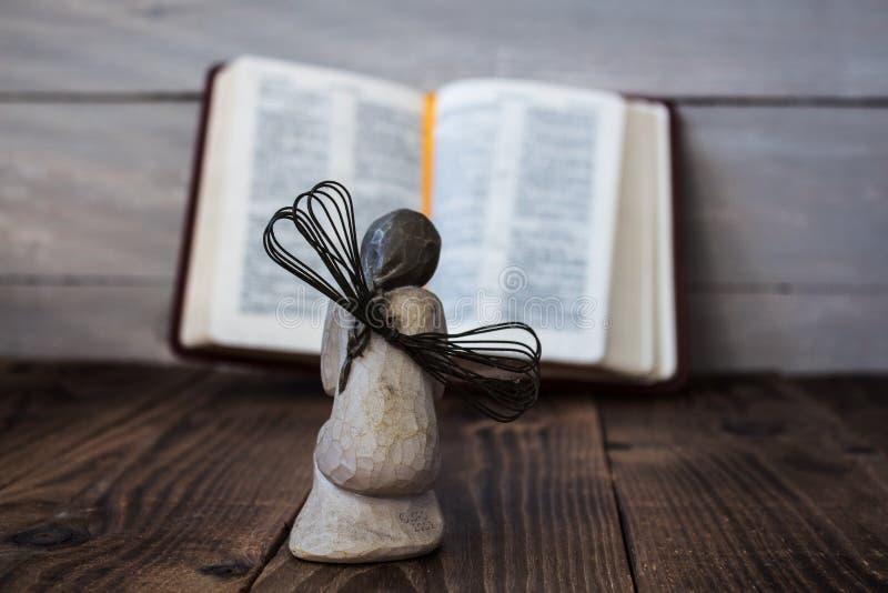 Engel und Bibel auf einem hölzernen Hintergrund lizenzfreie stockfotos