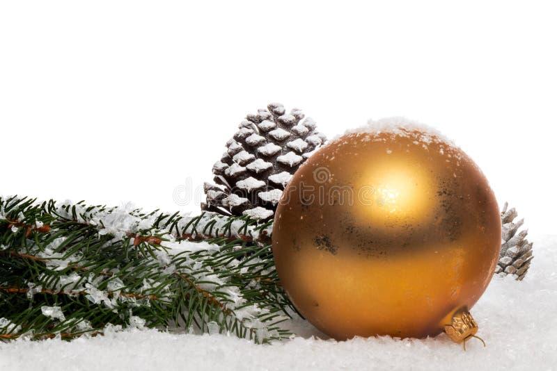 Engel und Christbaumkugel im Dekoschnee. Liegender Engel, Tannenzapfe und Tannengrün mit Weihnachtskugel in Dekoschnee royalty free stock photos