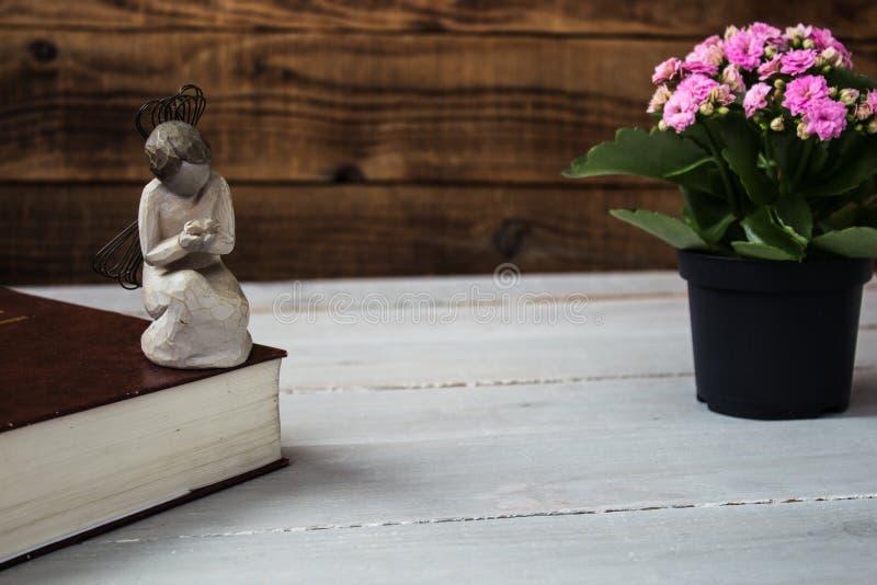Engel und die Bibel und die Blumen lizenzfreies stockfoto