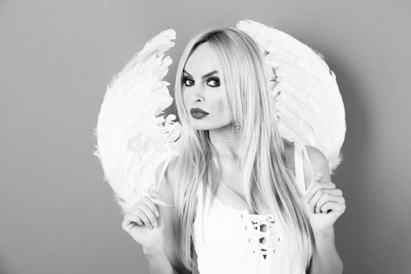 Engelachtige schoonheid mooie blondevrouw met engelenvleugels royalty-vrije stock fotografie