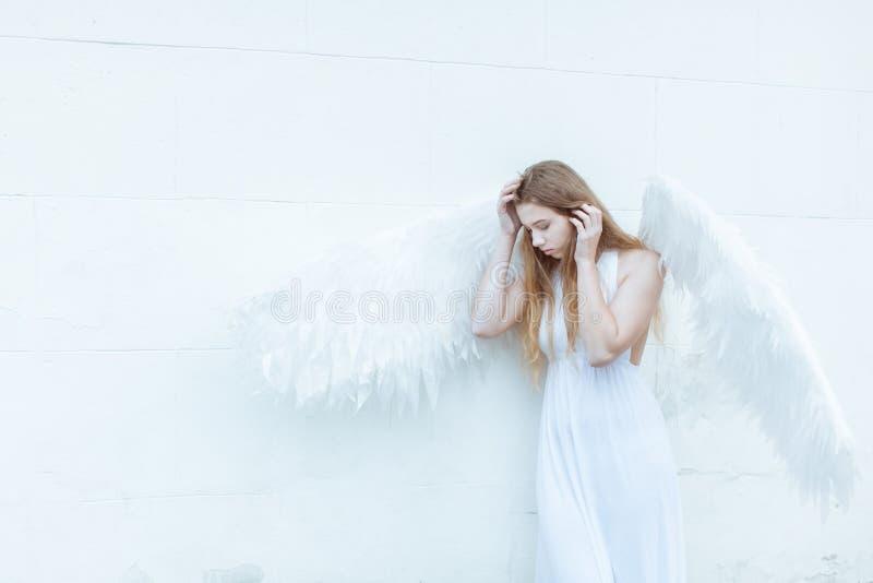 Engelenmeisje dichtbij muur stock foto