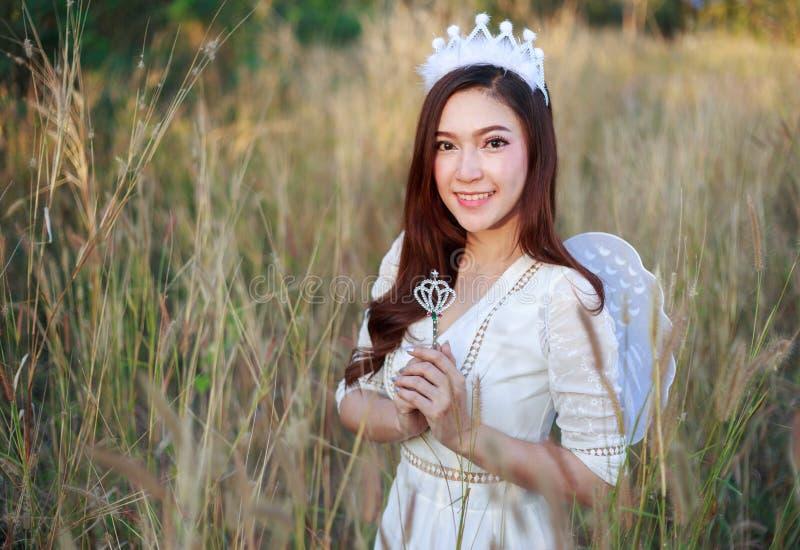 Engelenvrouw op een grasgebied met zonlicht stock foto