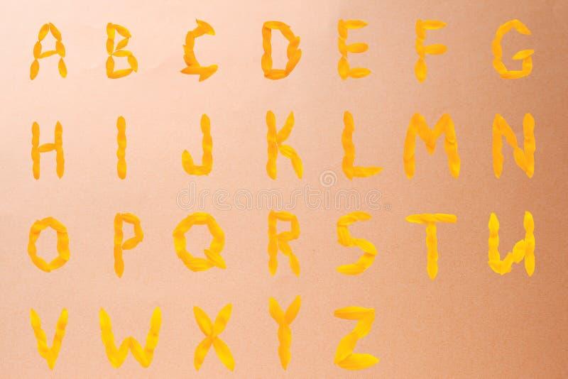 Engels alfabet van gele die brieven van zonnebloembloemblaadjes wordt gemaakt op een beige glanzende achtergrond stock foto's