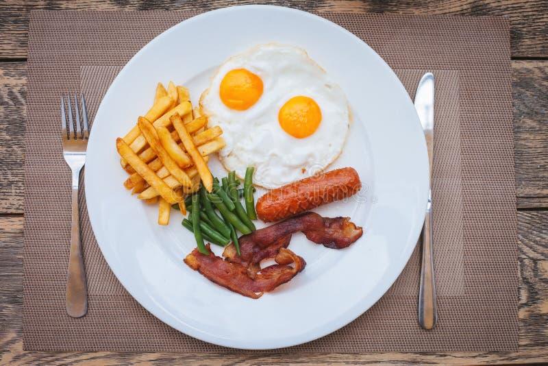 Engels ontbijt met gebraden eieren, bacon, worsten, slabonen en frieten stock foto's