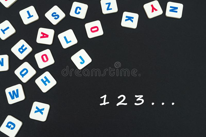 Engelse gekleurde vierkante die brieven op zwarte achtergrond met nummer 123 worden verspreid royalty-vrije stock afbeeldingen