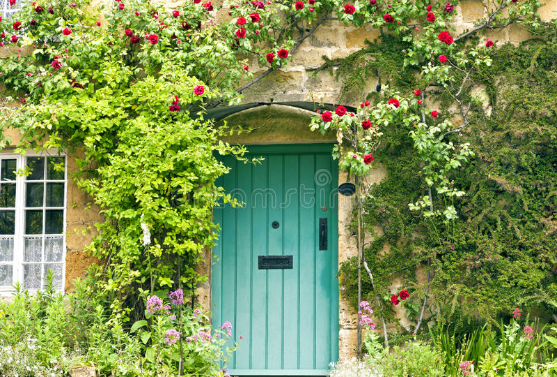 Engelse plattelandshuisje groene deuren en rode rozen stock foto