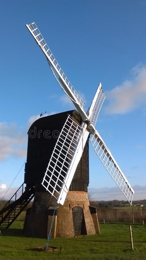 Engelse postwindmolen met baksteenrok, mening #1 stock afbeeldingen