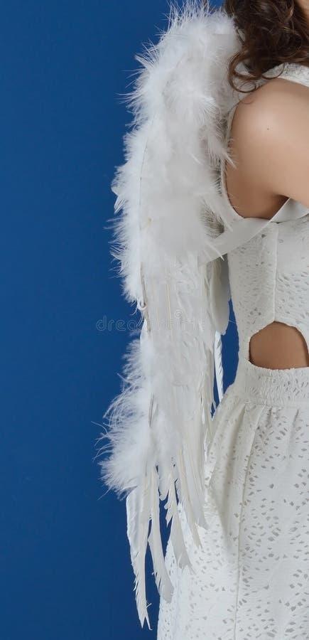 Engelsflügel weiß auf der Rückseite eines Mädchens in einem weißen Kleid, das seitlich auf einem blauen Hintergrund steht stockbilder