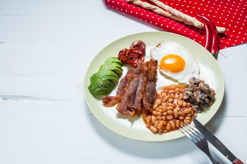 Engelsk frukost av bacon, stekt ägg, bönor, champinjoner, avokado royaltyfri bild
