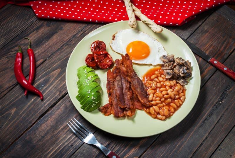Engelsk frukost av bacon, stekt ägg, bönor, champinjoner, avokado royaltyfri fotografi