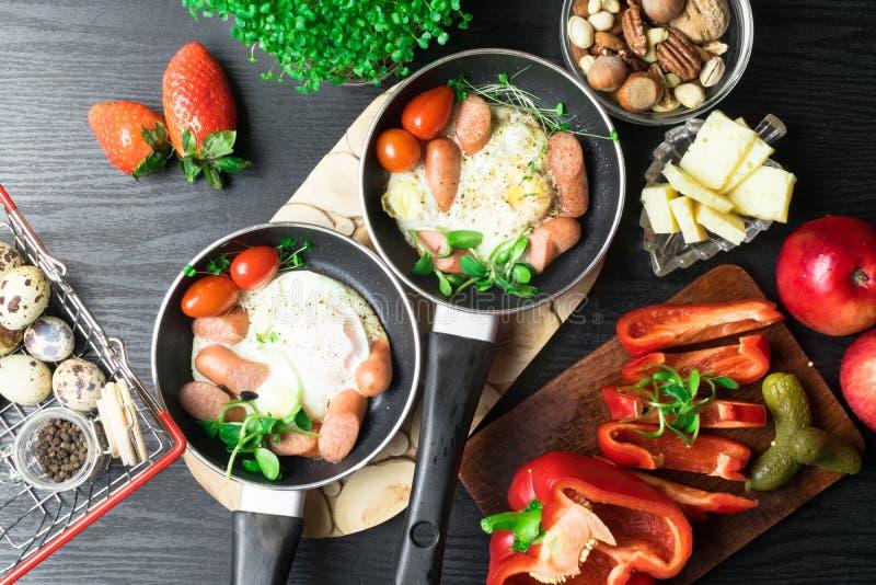Engelsk frukost för två Stekte ägg med korvar i en stekpanna med kryddor och nya grönsaker, jordgubbe fotografering för bildbyråer