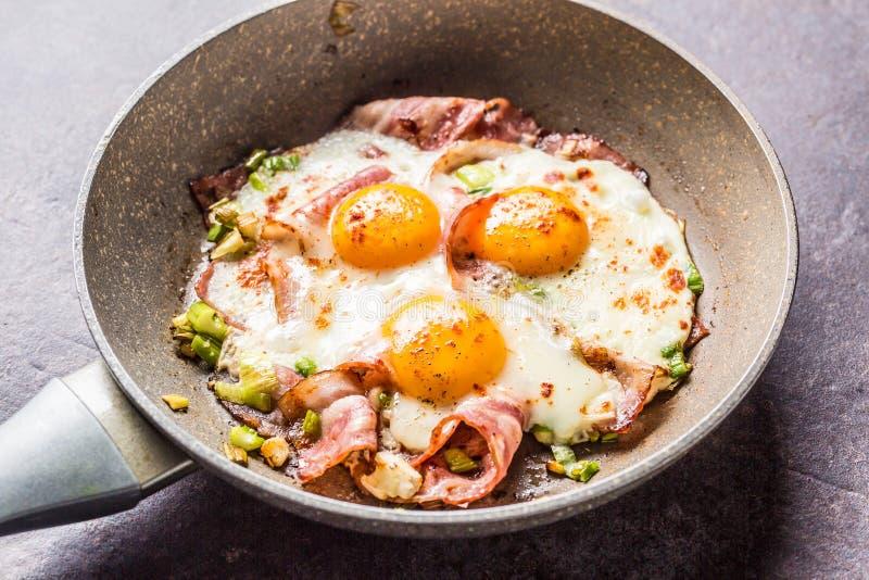 Engelsk frukost stekte baconskinka och ägg i keramisk panna arkivbild