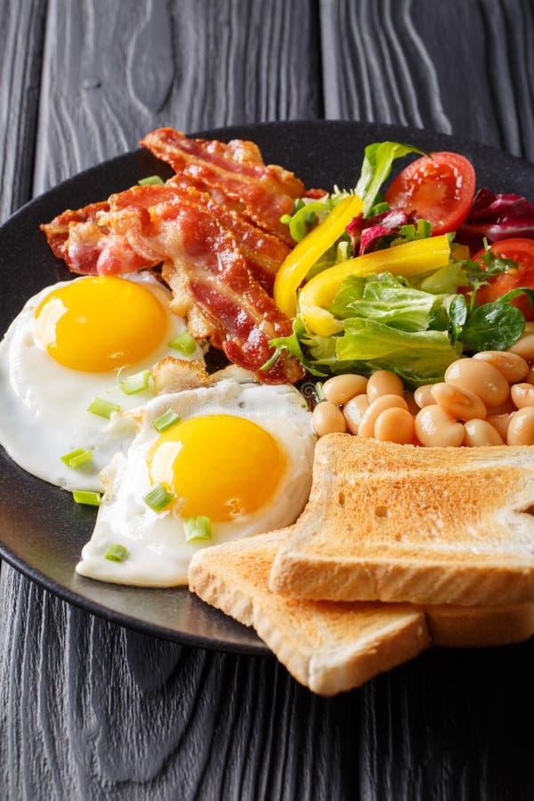 Engelsk hemlagad frukost: stekte ägg med bacon, bönor, rostat bröd royaltyfria foton