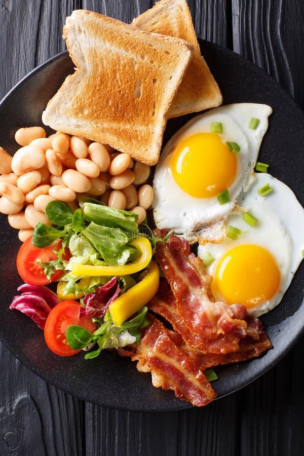 Engelsk hemlagad frukost: stekte ägg med bacon, bönor, rostat bröd arkivbild