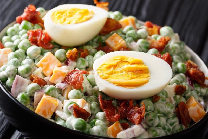 Engelsk påsksallad med ost för nya gröna ärtor, för kokta ägg, bacon- och cheddarmed såsnärbild i en bunke på tabellen royaltyfria bilder