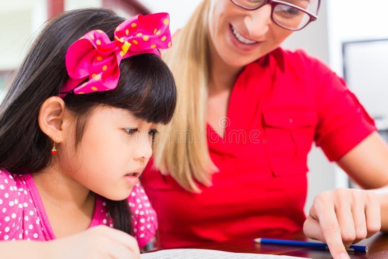 Engelsk privat lärare som arbetar med den asiatiska flickan royaltyfria bilder