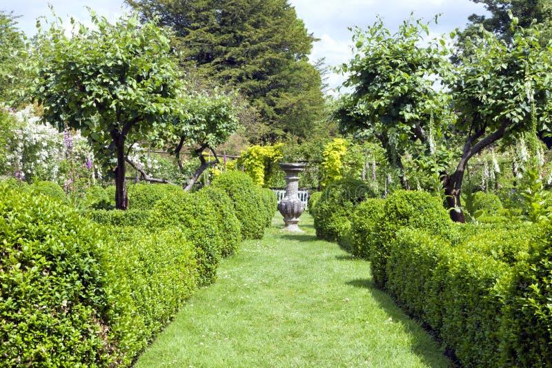 Engelsk sommarträdgård med den dekorativa krukan arkivfoton