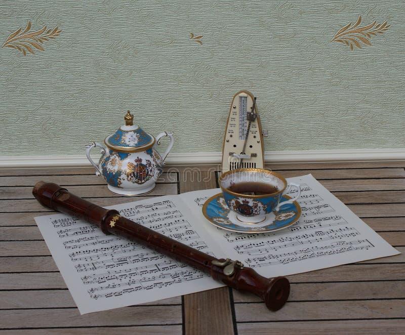 Engelsk tekopp med tefatet, sockerbunken, fint benporslinporslin, metronomen för musik och en kvarterflöjt på ett ark av musik arkivbilder