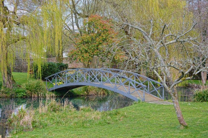 Engelsk trädgård med den dekorativa japanska bron royaltyfria foton