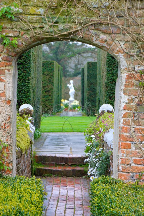 Engelsk trädgårdport med en marmoreal skulptur mellan buskar av askträd fotografering för bildbyråer
