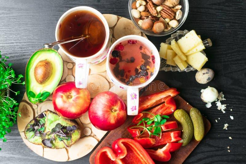Engelsk vård- frukost för två, vaktelägg och nya grönsaker, ost, muttrar, avokado, smörgås med avokado och basilika och te royaltyfria bilder