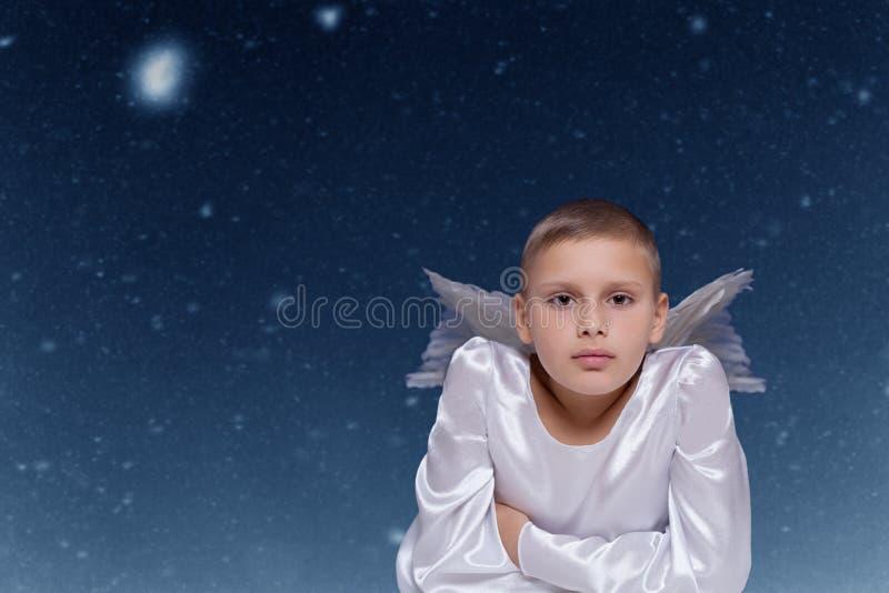 Engelskind gegen fallenden Schneehintergrund stockbild