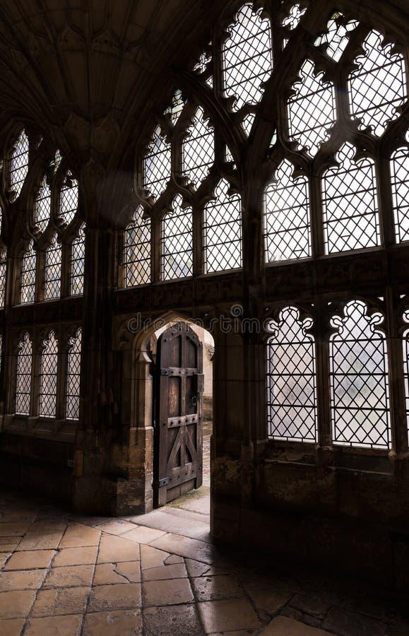 Engelskt domkyrkastengolv, väggar, exponeringsglas och ljust komma till och med gammal trädörr royaltyfri foto