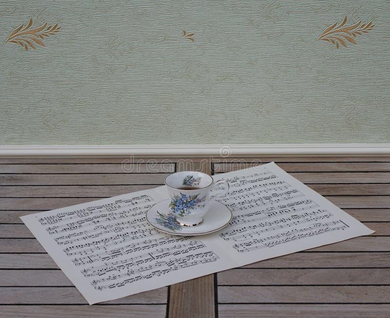 Engelskt tekopp och tefat med den blom- dekor- och silverkanten, på ett ark av musik royaltyfri foto