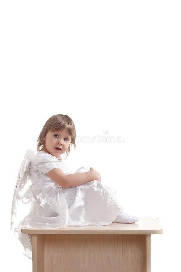 Engelsmädchen, das auf Bedienpult sitzt stockfoto