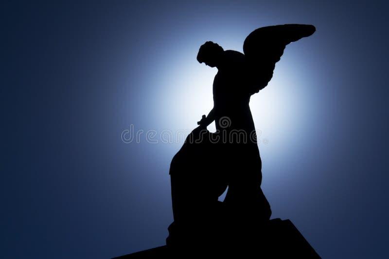 Engelsschattenbild von einem hintergrundbeleuchteten in einem Kirchhof. lizenzfreie stockfotografie