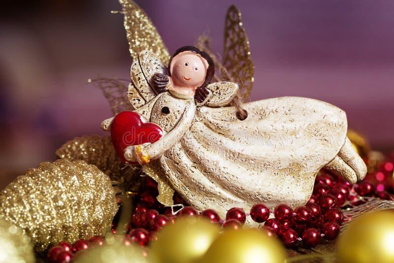 Engelsspielzeug mit einem Herzen in der Hand auf einem Weihnachtshintergrund christ lizenzfreie stockfotografie
