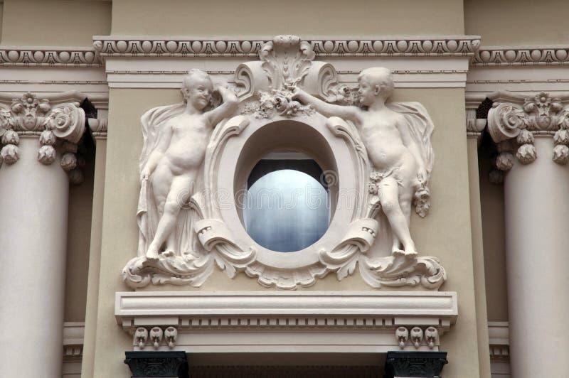Engelsstatuen und ovales Fenster an der barocken Artfassade stockbilder