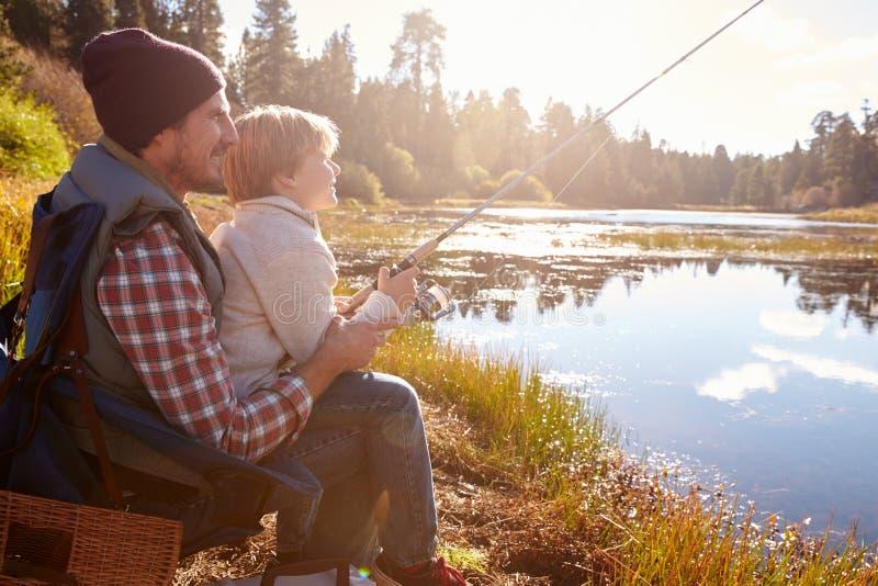 Engendre al hijo de enseñanza para pescar sentarse en la orilla del lago imagenes de archivo