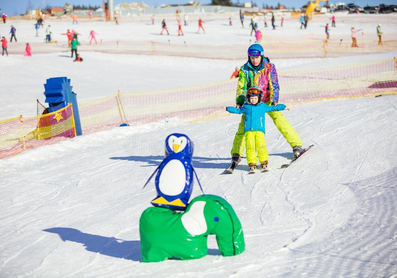 Engendre al pequeño hijo de enseñanza para esquiar en el área de los niños imágenes de archivo libres de regalías