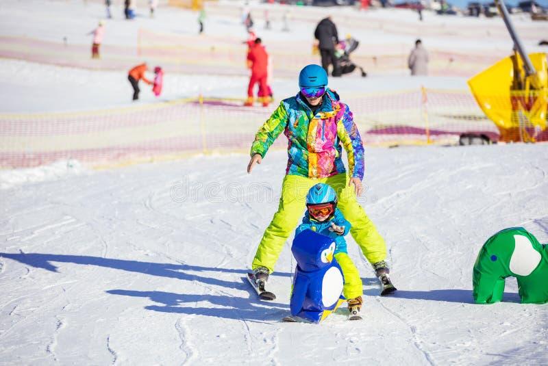 Engendre al pequeño hijo de enseñanza para esquiar en el área de los niños el invierno r foto de archivo libre de regalías