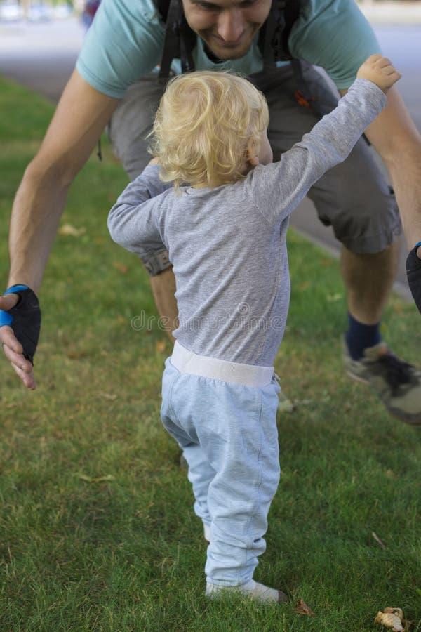 Engendre cercar a su bebé, niño que aprende caminar imagen de archivo