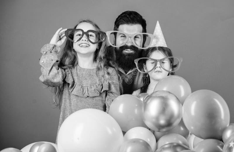 Engendre con dos hijas que se divierten Concepto de la paternidad Familia amistosa llevar los accesorios divertidos del partido E fotografía de archivo