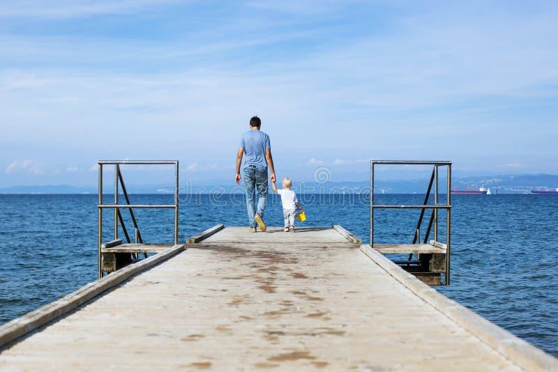 Engendre con el hijo que camina en el embarcadero del mar foto de archivo