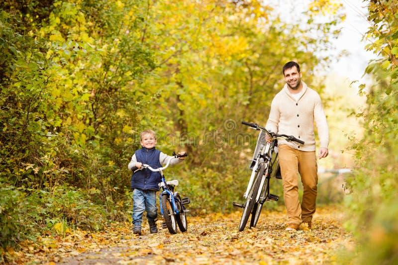 Engendre con el pequeño hijo que completa un ciclo en parque del otoño fotografía de archivo