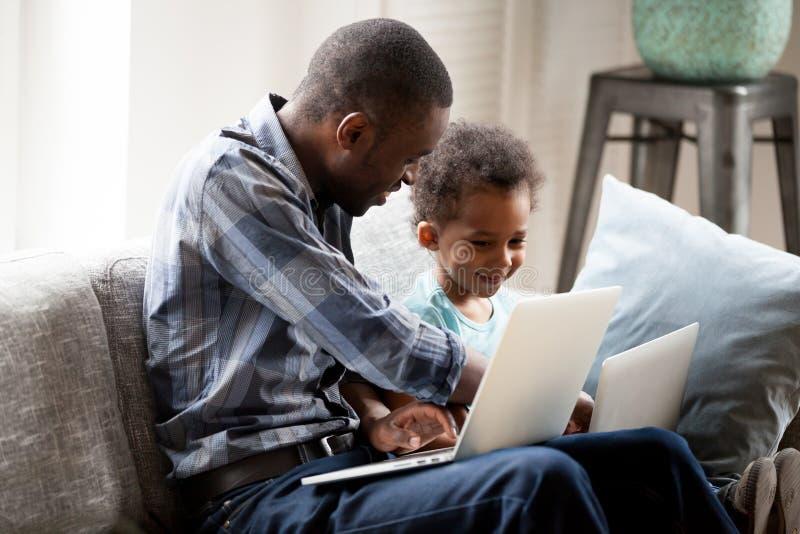 Engendre con el pequeño hijo que usa los ordenadores que se sientan en el sofá foto de archivo libre de regalías
