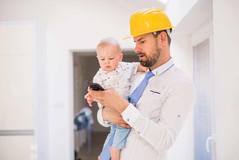 Engendre con la camisa, el lazo, el casco y el smartphone deteniendo a un hijo del bebé en casa fotos de archivo libres de regalías