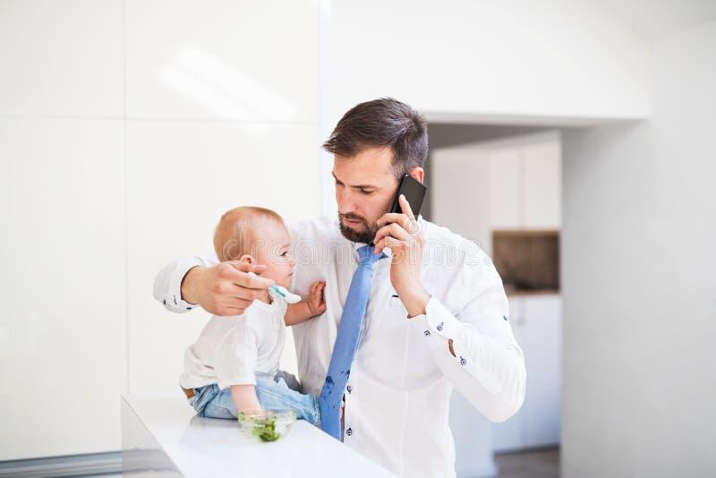 Engendre con la camisa y ate y smartphone que alimenta a un hijo del bebé en casa, al hablar en el teléfono fotografía de archivo