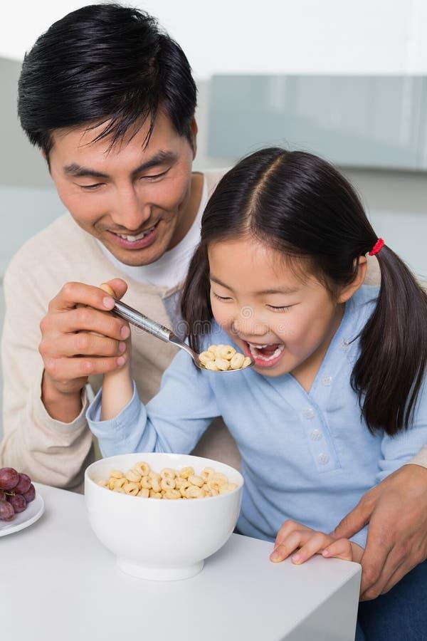 Engendre con la hija joven que come cereales en cocina fotografía de archivo