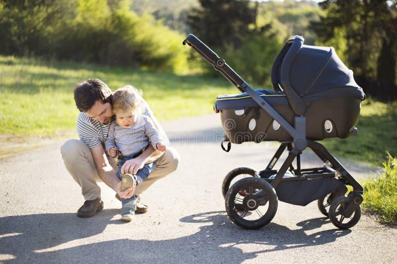 Engendre con la pequeña hija del hijo y del bebé en cochecito Parque soleado fotos de archivo