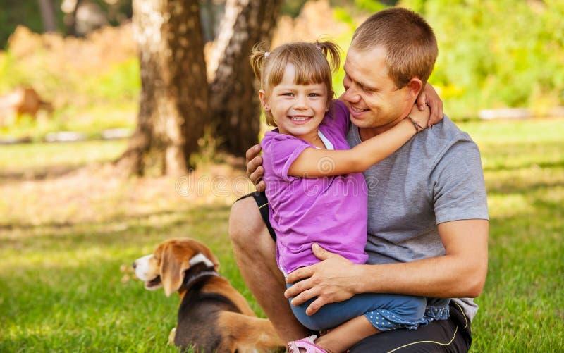 Engendre con la pequeña hija en el prado verde fotografía de archivo