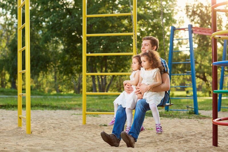 Engendre con los niños que juegan en un oscilación en el patio fotografía de archivo libre de regalías