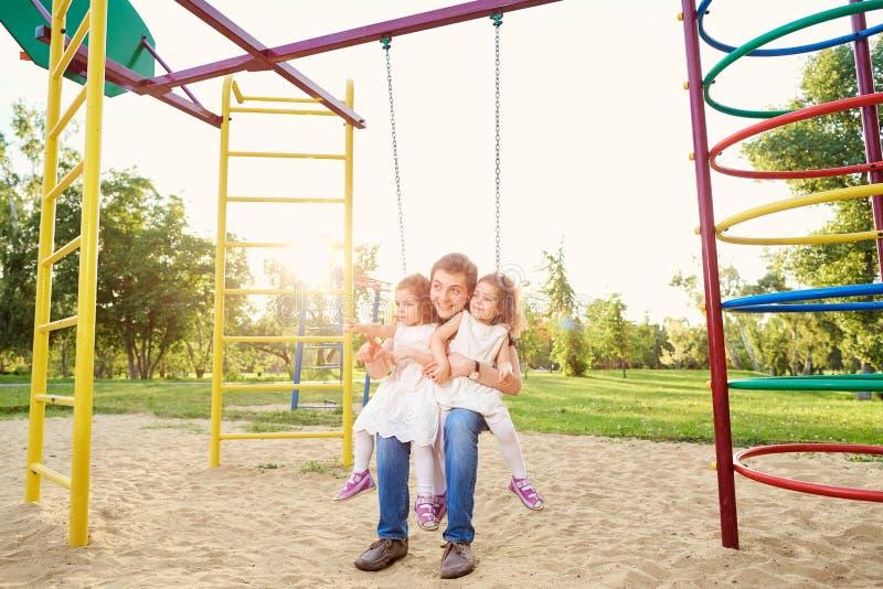 Engendre con los niños que juegan en un oscilación en el patio imagenes de archivo